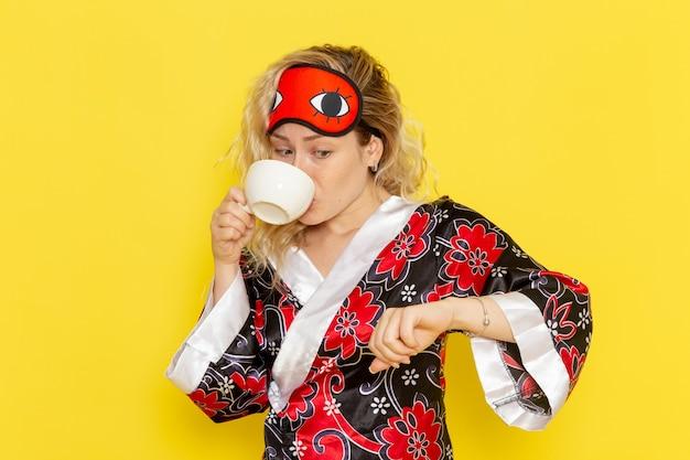 Widok z przodu młoda kobieta w szacie nocnej i nosząc maskę na oczy przygotowuje się do snu pijąc kawę na żółtej ścianie snu modelki łóżko nocne
