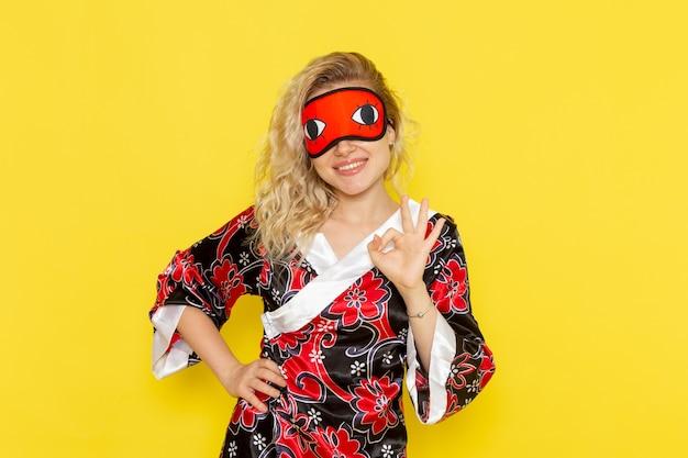 Widok z przodu młoda kobieta w szacie nocnej i noszącej maskę na oczy przygotowuje się do snu pozuje i uśmiecha się na żółtej ścianie spać kobietę ciemność kolor noc