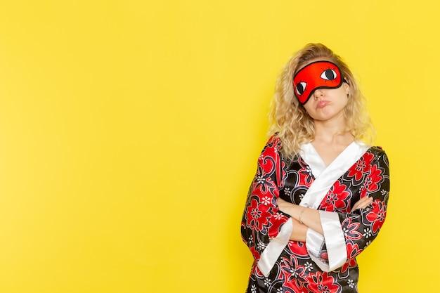 Widok z przodu młoda kobieta w szacie nocnej i noszącej maskę na oczy przygotowuje się do snu pozuje na żółtej ścianie nocny sen kobiet w kolorze ciemności