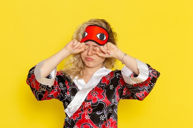 Widok z przodu młoda kobieta w szacie nocnej i noszącej maskę na oczy przygotowuje się do snu zmęczona na jasnożółtej ścianie snu modelka nocna łóżko