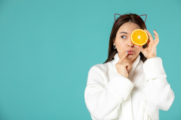 Widok z przodu młoda kobieta w szlafroku trzymająca plasterek pomarańczy na niebieskim tle