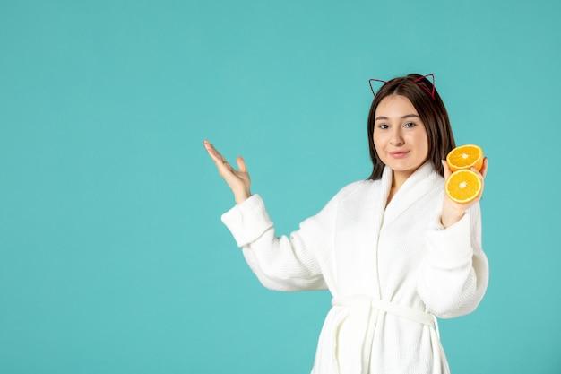 Widok z przodu młoda kobieta w szlafroku trzymająca plasterki pomarańczy na niebieskim tle prysznic uroda skóra masująca kobieta maska samoopieka pocałunek spa