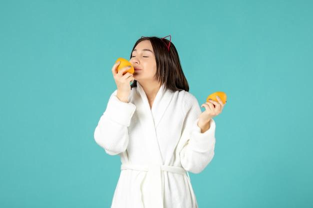 Widok z przodu młoda kobieta w szlafroku trzymająca plasterki pomarańczy na niebieskim tle
