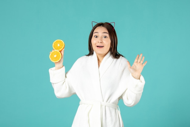 Widok z przodu młoda kobieta w szlafroku trzymająca pokrojoną pomarańczę na niebieskim tle
