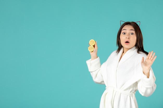 Widok z przodu młoda kobieta w szlafroku trzymająca pokrojone cytryny na niebieskim tle