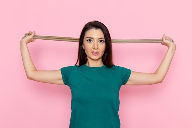 Widok z przodu młoda kobieta w zielonej koszulce liny dla sportu na różowej ścianie w talii ćwiczenia sportowe ćwiczenia piękna szczupła atleta