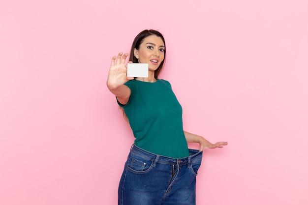 Widok z przodu młoda kobieta w zielonej koszulce trzyma białą kartę na jasnoróżowej ścianie w talii ćwiczenia sportowe piękna szczupła kobieta