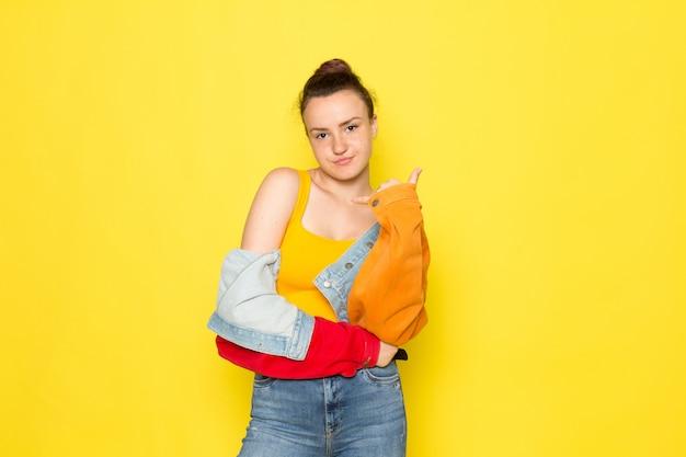 Widok z przodu młoda kobieta w żółtej koszuli kolorowej kurtce i niebieskich dżinsach tylko pozuje