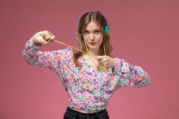 Widok z przodu młoda kobieta wyciągając jej słuchawki kolory niebieski i żółty
