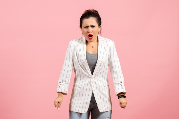 Widok z przodu młoda kobieta z białą kurtką i gniewną twarzą na różowym tle dama emocje moda kolor uczucie kobieta