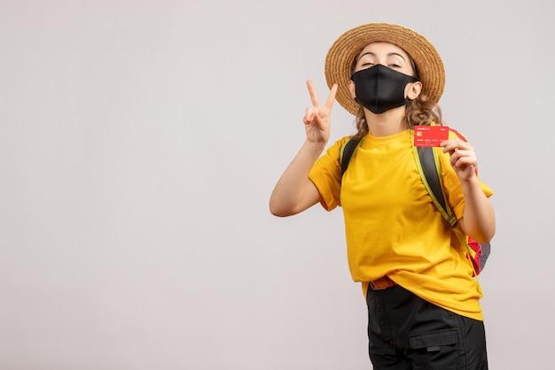 Widok z przodu młoda kobieta z czarną maską trzymająca kartę czyniącą znak zwycięstwa