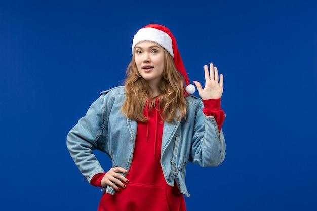 Widok z przodu młoda kobieta z czerwoną czapką na jasnoniebieskim tle emocji bożego narodzenia