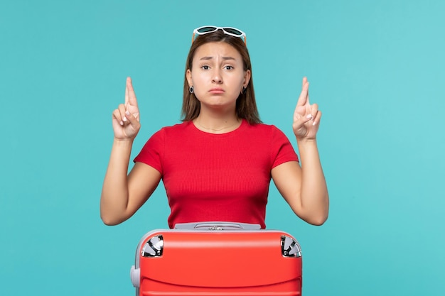 Widok z przodu młoda kobieta z czerwoną torbą krzyżując palce na niebieskiej przestrzeni