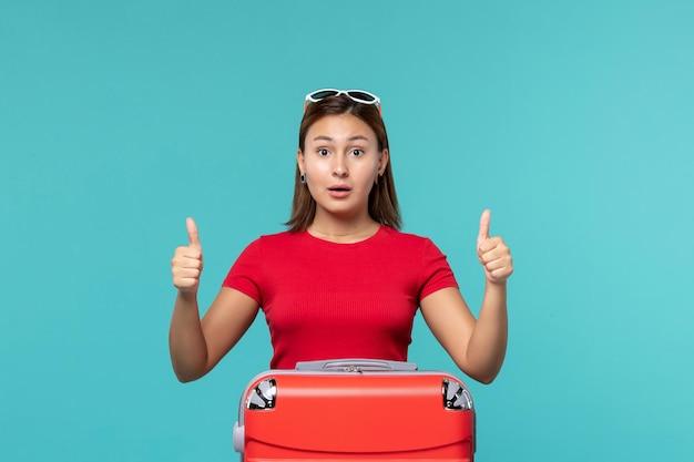 Widok z przodu młoda kobieta z czerwoną torbą przygotowuje się do wakacji na jasnoniebieskiej przestrzeni