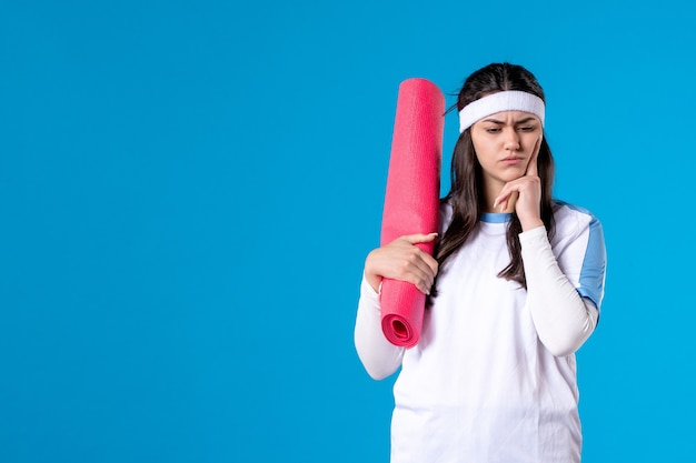 Widok z przodu młoda kobieta z dywanem do ćwiczeń na niebieskiej ścianie