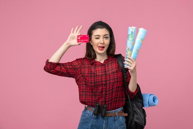 Widok z przodu młoda kobieta z kartą bankową i mapami na różowym tle kolor ludzkiej kobiety
