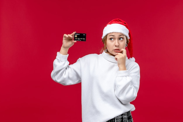 Widok z przodu młoda kobieta z kartą bankową na czerwonym tle