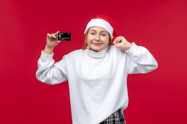 Widok z przodu młoda kobieta z kartą bankową na jasnoczerwonym tle
