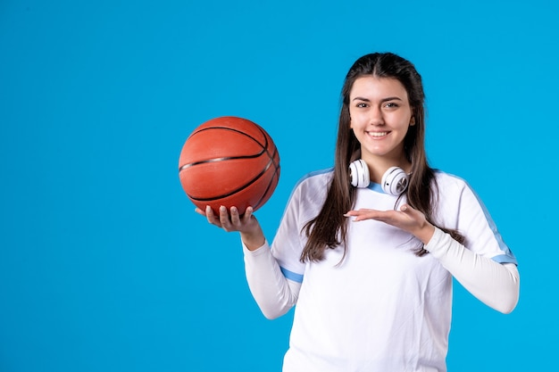 Widok z przodu młoda kobieta z koszykówką na niebieskiej ścianie