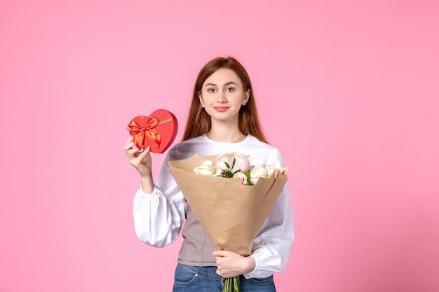 Widok z przodu młoda kobieta z kwiatami i obecny jako prezent na dzień kobiet na różowym tle poziomy marsz kobieta data równość róża miłość zmysłowa kobiecość