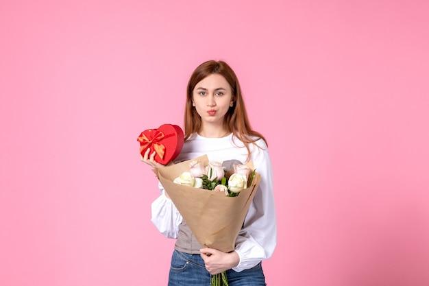 Widok z przodu młoda kobieta z kwiatami i obecny jako prezent na dzień kobiet na różowym tle róża pozioma marca data kobieca miłość równość