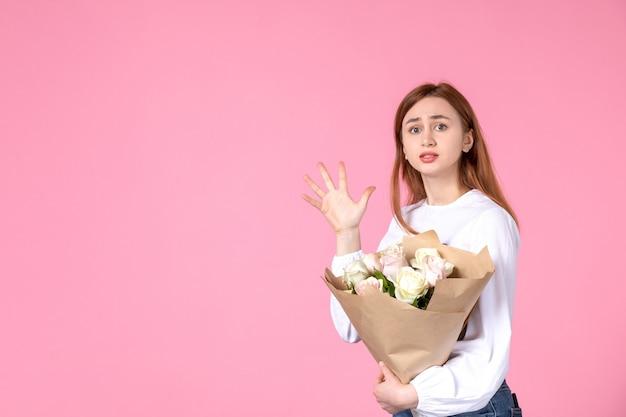 Widok z przodu młoda kobieta z kwiatami jako dzień kobiet obecny na różowym tle poziomy kobiecy marsz miłość kobieta zmysłowa róża równości