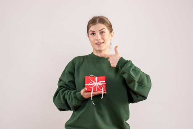 Widok z przodu młoda kobieta z małym prezentem świątecznym