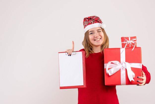 Widok z przodu młoda kobieta z małymi prezentami i notatką