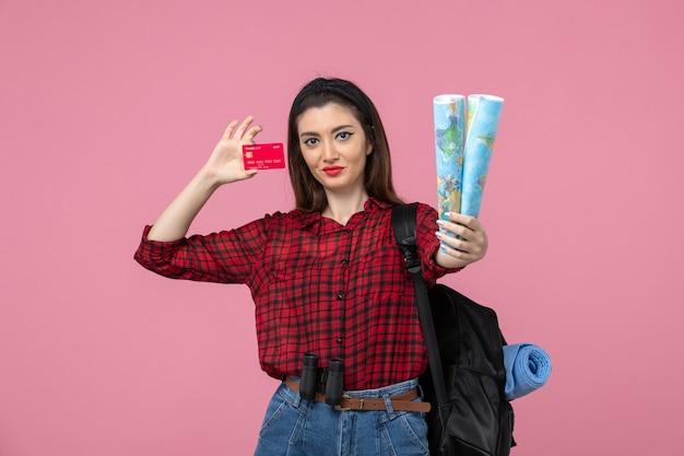 Widok z przodu młoda kobieta z mapami i kartą bankową na różowym tle kobieta ludzki kolor