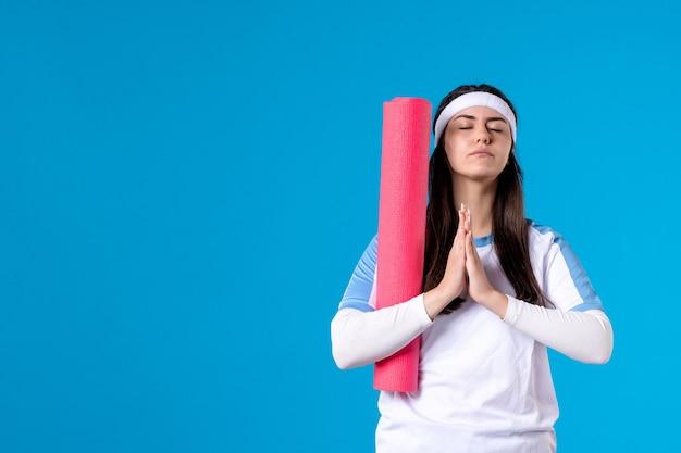 Widok z przodu młoda kobieta z matą do jogi na niebieskiej ścianie