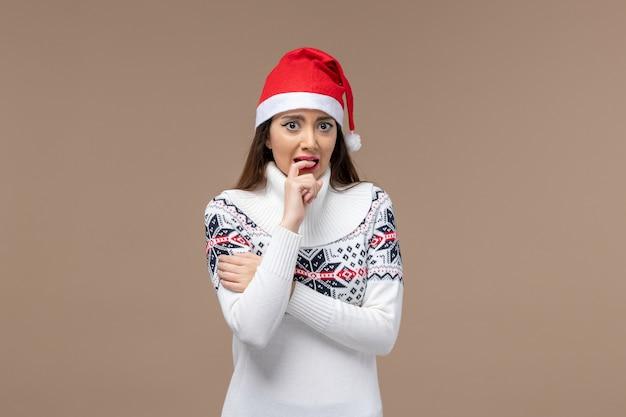 Widok z przodu młoda kobieta z nerwowym wyrazem na brązowym tle emocje nowego roku boże narodzenie
