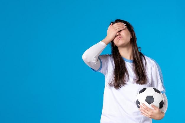Widok z przodu młoda kobieta z piłką nożną na niebieskiej ścianie