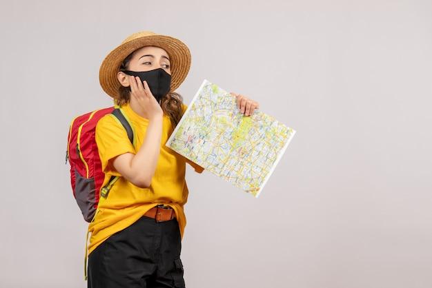 Widok z przodu młoda kobieta z plecakiem trzymającym mapę