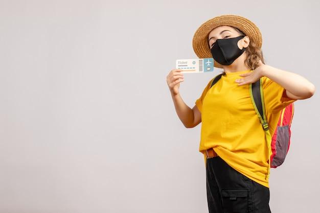 Widok z przodu młoda kobieta z plecakiem w czarnej masce trzymająca bilet podróżny