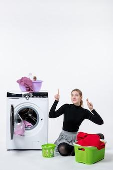 Widok z przodu młoda kobieta z pralką i brudnymi ubraniami na białej ścianie