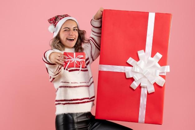 Widok z przodu młoda kobieta z prezentami bożonarodzeniowymi