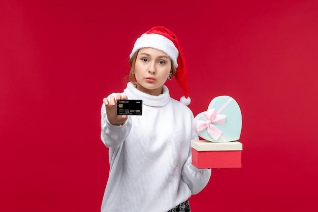 Widok z przodu młoda kobieta z prezentami i kartą bankową na czerwonym tle