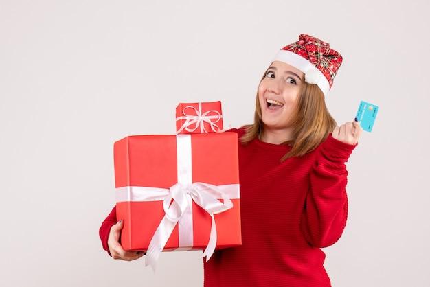 Widok z przodu młoda kobieta z prezentami świątecznymi i kartą bankową