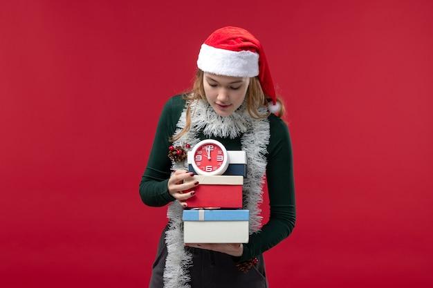 Widok z przodu młoda kobieta z prezentami z zegarem na czerwonym tle