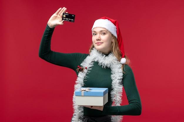 Widok z przodu młoda kobieta z prezentem i kartą bankową na czerwonym tle