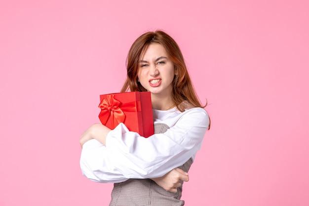 Widok z przodu młoda kobieta z prezentem w czerwonym opakowaniu na różowym tle data marca pozioma miłość równość kobiety