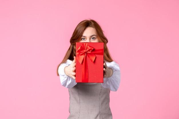 Widok z przodu młoda kobieta z prezentem w czerwonym opakowaniu na różowym tle data miłości marzec poziome zmysłowy prezent perfumy równość kobieta zdjęcie pieniądze