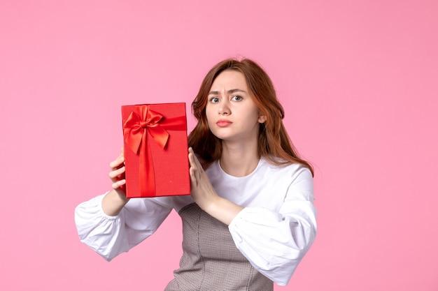 Widok z przodu młoda kobieta z prezentem w czerwonym opakowaniu na różowym tle data miłości marzec poziome zmysłowy prezent perfumy równość kobieta zdjęcie
