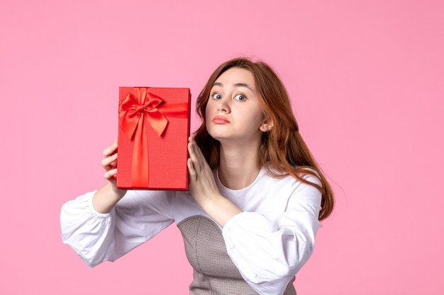 Widok z przodu młoda kobieta z prezentem w czerwonym opakowaniu na różowym tle data miłości marzec poziome zmysłowy prezent perfumy równość zdjęcie pieniądze