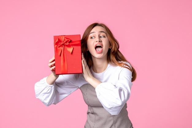 Widok z przodu młoda kobieta z prezentem w czerwonym opakowaniu na różowym tle data miłości marzec poziome zmysłowy prezent równość kobieta zdjęcie pieniądze