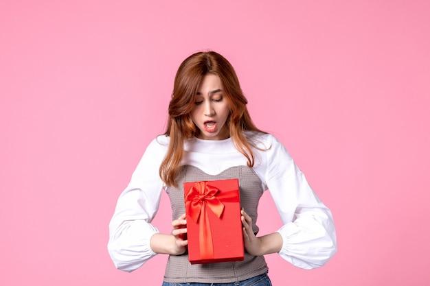 Widok z przodu młoda kobieta z prezentem w czerwonym opakowaniu na różowym tle marsz poziomy zmysłowy prezent zdjęcie równości kobieta perfumy