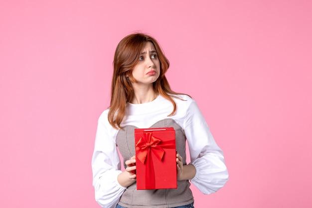 Widok z przodu młoda kobieta z prezentem w czerwonym opakowaniu na różowym tle marzec poziome zmysłowy prezent perfumy zdjęcie pieniądze kobieta