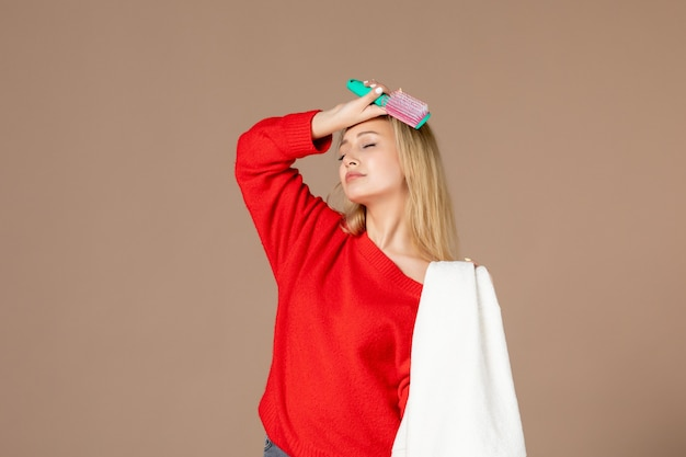 Widok z przodu młoda kobieta z ręcznikiem i szczotką do włosów na ciemnym różowym tle