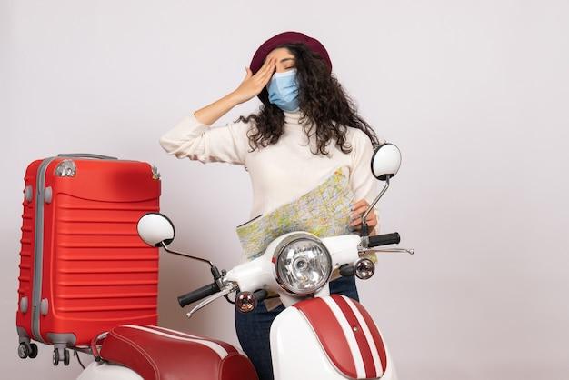 Widok z przodu młoda kobieta z rowerem w masce trzymająca mapę na białym tle kolor wirusa prędkość covid- motocykl pandemiczny pojazd