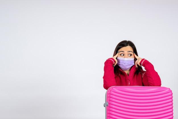 Widok z przodu młoda kobieta z różową torbą w masce na białej ścianie wakacje pandemiczny wirus covid-kolor kobieta